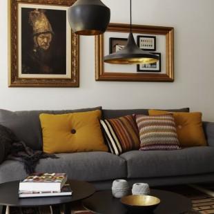 siva sofa sa žutim i narandžastim jastucima